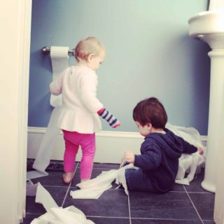 toddlers playing with toilet paper