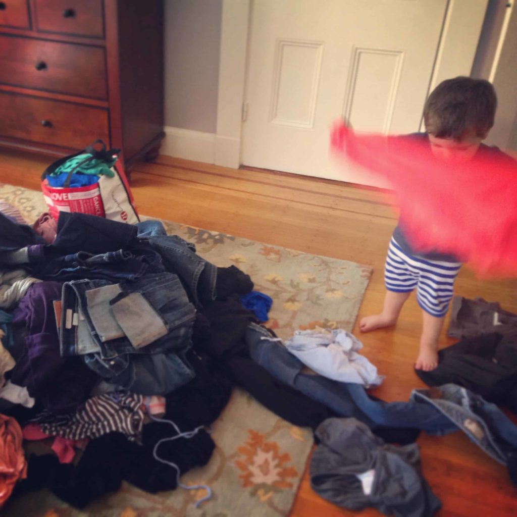 toddler playing in laundry pile