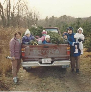 kids in a pickup truck getting Christmas trees