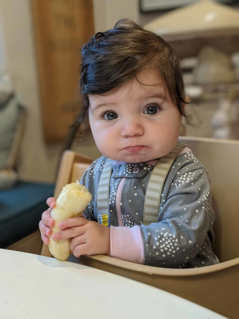 baby eating a banana in a Tripp Trapp chair