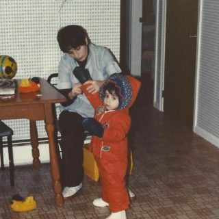 mom putting a snowsuit on a child