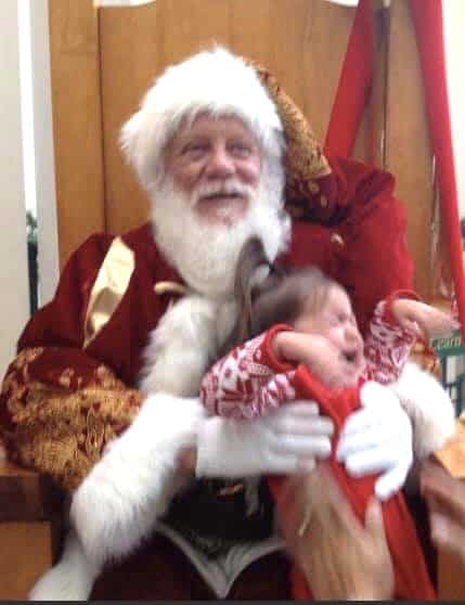 child flailing off Santas lap during photo