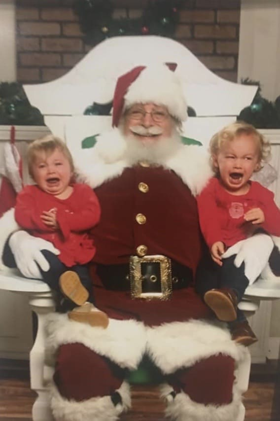 Santa holding 2 crying kids
