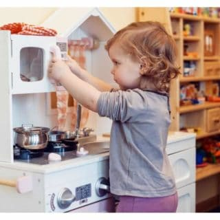 little girl playing with pretend kitchen