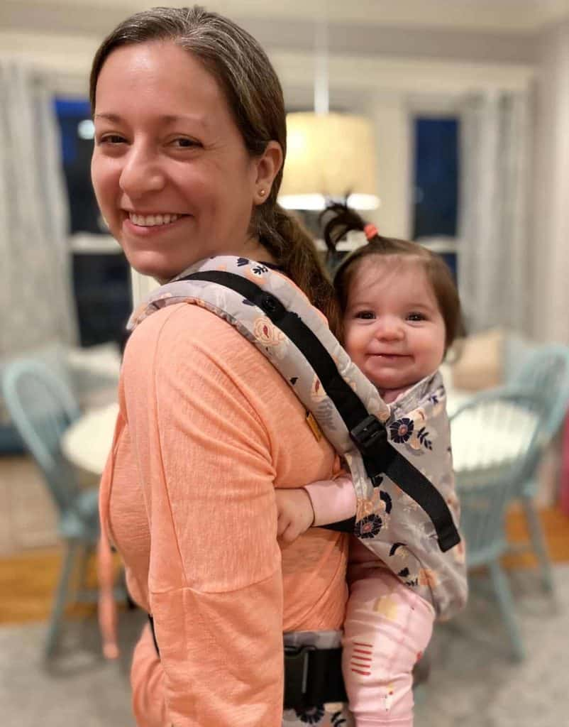 Mom and baby in a Tula Free to Grow carrier, using the back-carry position