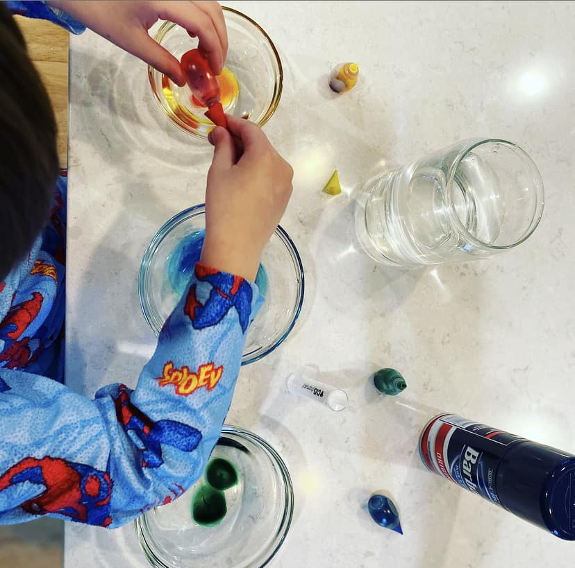 boy adding food coloring to small glass jars
