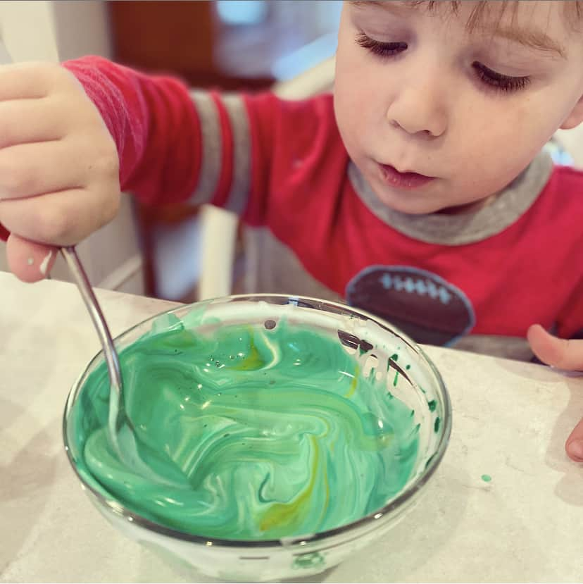 toddler playing with colored shaving cream