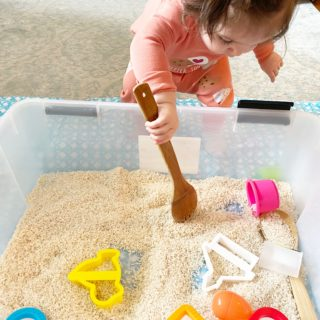 toddler playing with a sensory rice bin