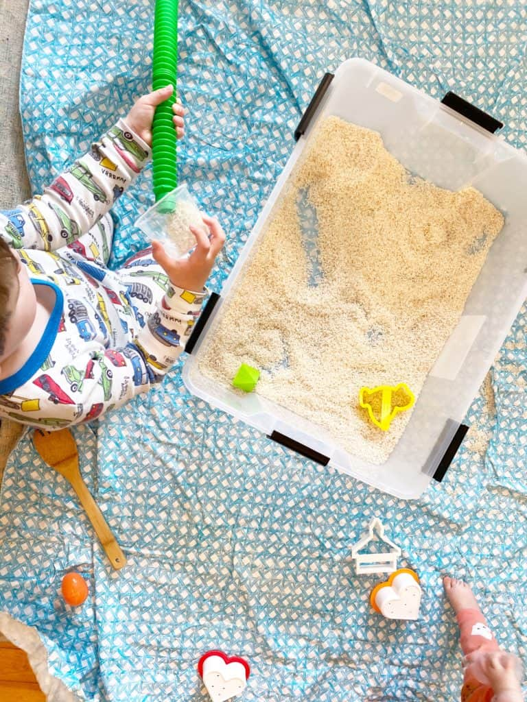 toddler playing with sensory bin filled with rice