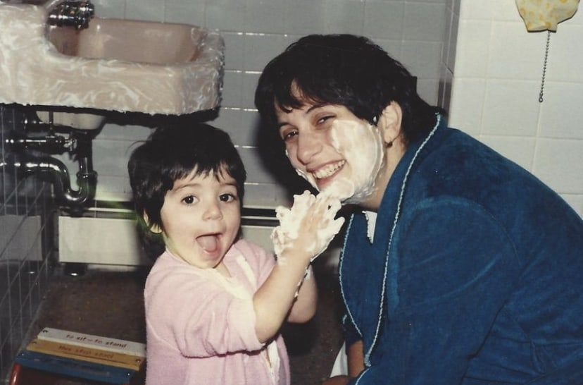 little girl covering her mom's face with shaving cream playfully