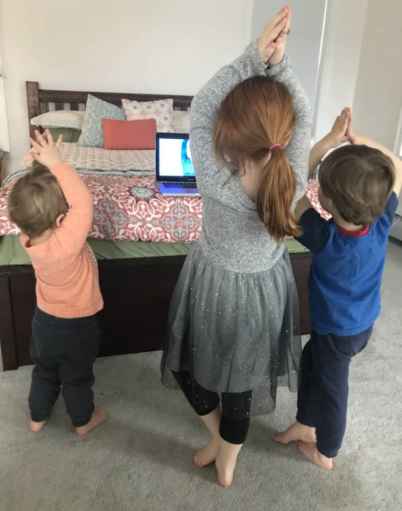 Three kids doing a yoga video. Yoga has many benefits for children, including its ability to improve balance for toddlers.