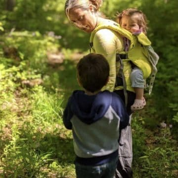 Mom hiking with two kids and baby in baby carrier