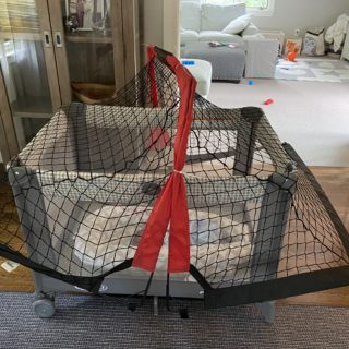 pack and play with portable soccer net over it