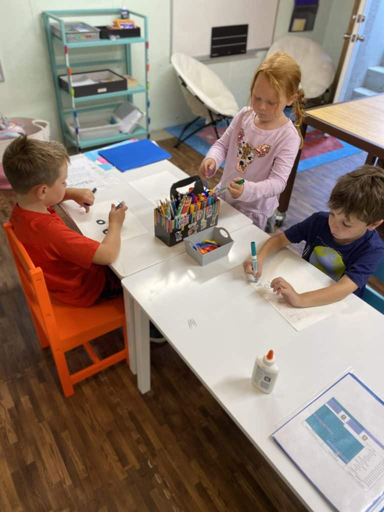3 kids working together at an arts and crafts table