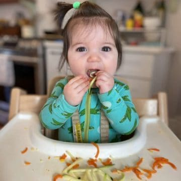 baby eating messy food in tripp trapp high chair