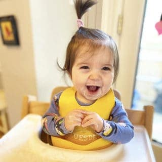 happy baby in yellow bib in tripp trapp chair